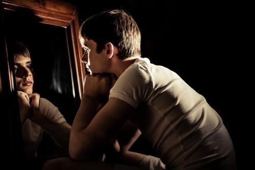Chłopak patrzy w lustro i zastanawia się