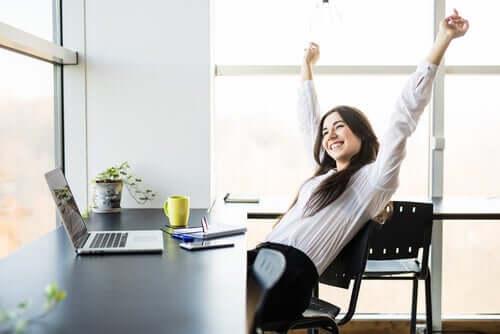 Szczęśliwa kobieta rozciąga sięprzy biurku