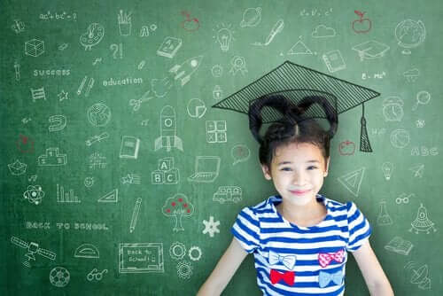 Dziewczynka uczy się przy zielonej tablicy szkolnej i czapką absolwenta