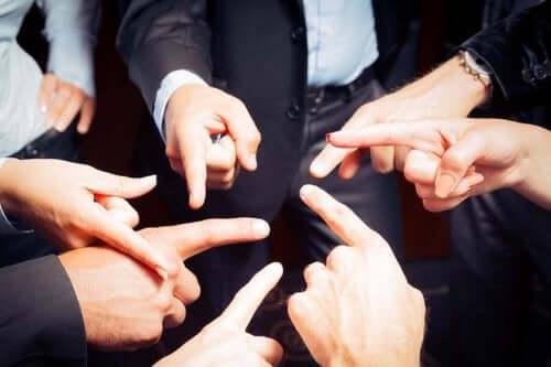 Grupa ludzi wskazujących na siebie palcami