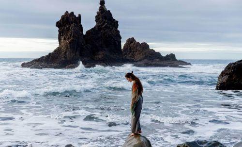 Kobieta stoi ze spuszczoną głową na skale na wzburzonym morzu