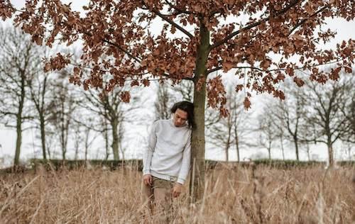 Mężczyzna oparty o drzewo