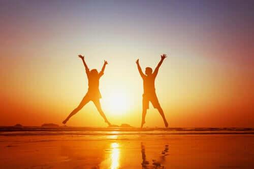 Szczęśliwa para skacze nad morzem