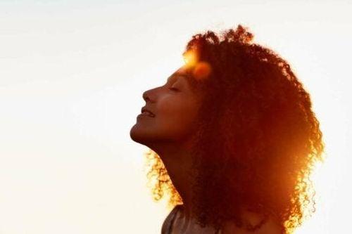 Zrelaksowana kobieta w promienaich zachodzącego słońca