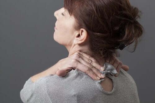 Kobieta chwyta się za kark z powodu bólu szyi