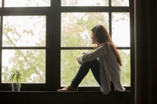 Kobieta siedzi przy oknie i rozmyśla nad swoim życiem