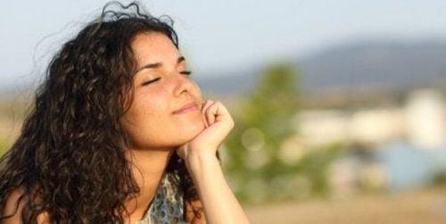 Kobieta uśmiecha się i z zamkniętymi oczyma o zachodzie słońca
