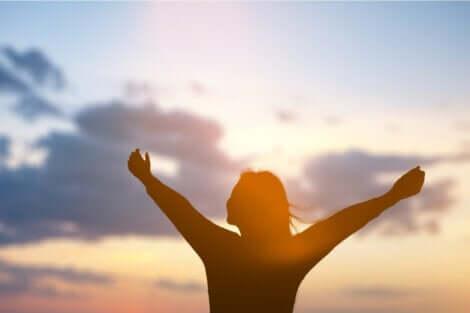 Kobieta z rozpostartymi ramionami na tle słońca
