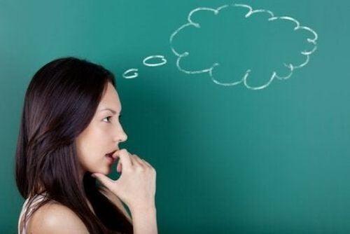 Kobieta zastanawia się przy zielonej tablicy