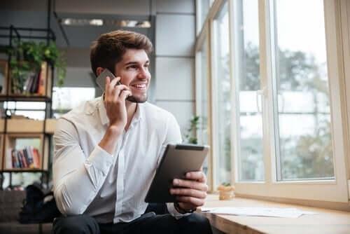 Mężczyzna jednocześnie korzysta z telefonu i tabletu - zapracowani przedsiębiorcy