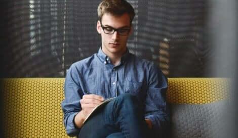 Mężczyzna w okularach siedzący na kanapie