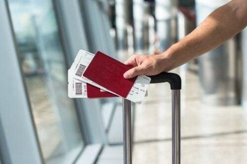 Osoba z walizką na lotnisku z dwoma paszportami w dłoni