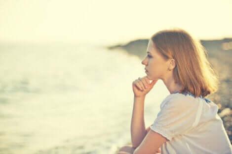 Zamyślona kobieta patrząca na wodę