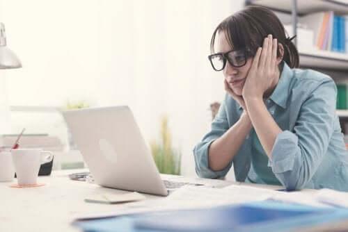 Znudzona kobieta w okularach podbiera głowę na rękach i myśli przed komputerem