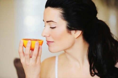 Kobieta wąchająca pomarańcza - uważne jedzenie
