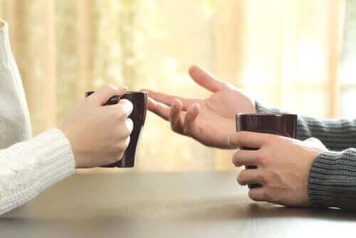 Dwie osoby rozmawiają, trzymając kubki - ich ręce