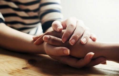 Dwie osoby trzymające dłonie - światu potrzeba więcej współczucia