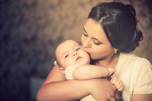 Kobieta całuje niemowlę w policzek