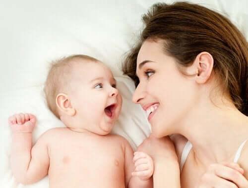 Matka i noworodek uśmiechają się do siebie szczęśliwi - więż dziecka z rodzicem