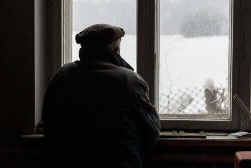 Starszy mężczyzna patrzący przez okno