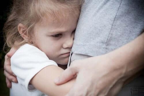 Dziewczynka przytula rodzica z niepokojem na twarzy
