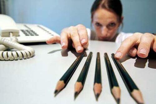 Kobieta pieczołowicie układa ołówki na biurku