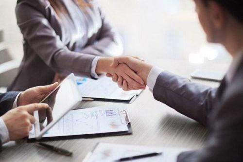 Ludzie podają sobie rękę na spotkaniu biznesowym