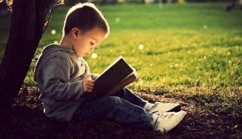 Male dziecko czyta grubą książkę, siedząc pod drzewem