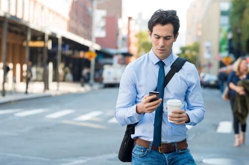 Smartfonowe zombie - mężczyzna patrzy na telefon, idąc ulicą