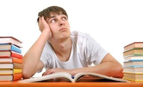 Znudzony student pośród stosów książek