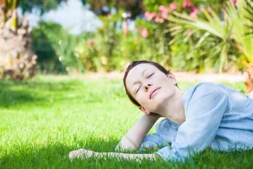 Kobieta odpoczywa z zamkniętymi oczyma na trawniku