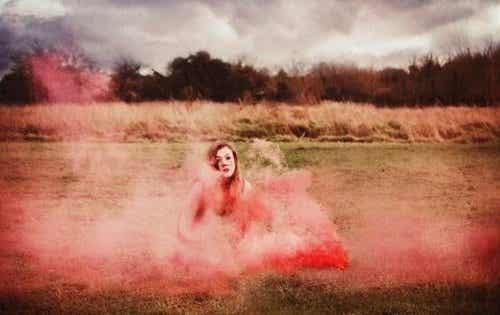 Kobieta otoczona różowym dymem na środku pola