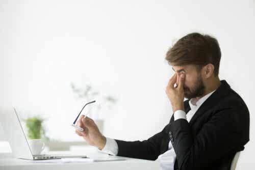 Mężczyzna przyciska palce do zmęczonych oczu w pracy