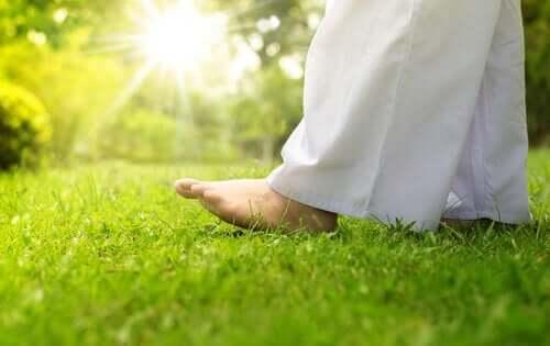 Osoba w białej sukni idzie boso po trawie