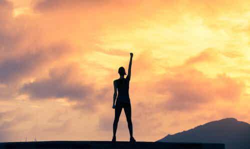 Osoba podnosząca ramię na tle pomarańczowego nieba