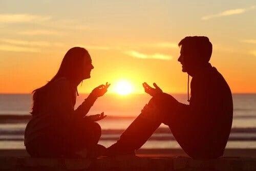 Para rozmawia na tle zachodu słońca