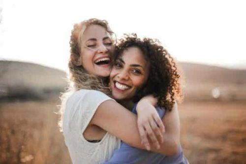 Dwie uśmiechnięte przyjaciółki we wzajemnym uścisku