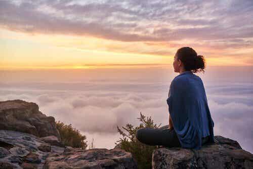 Kobieta siedząca na czubku góry - jak doceniać swój wysiłek?
