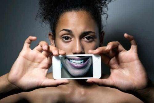 Kobieta zakrywa sobie twarz sztucznym uśmiechem na ekranie telefonu