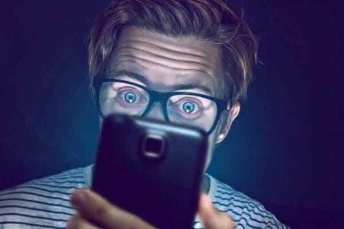 Zdziwiony mężczyzna patrzy na telefon późno w nocy