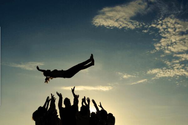 Grupa osób łapiąca spadającą kobietę