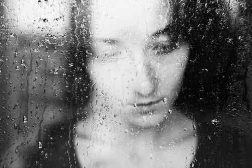 Kobieta za szybą z deszczem