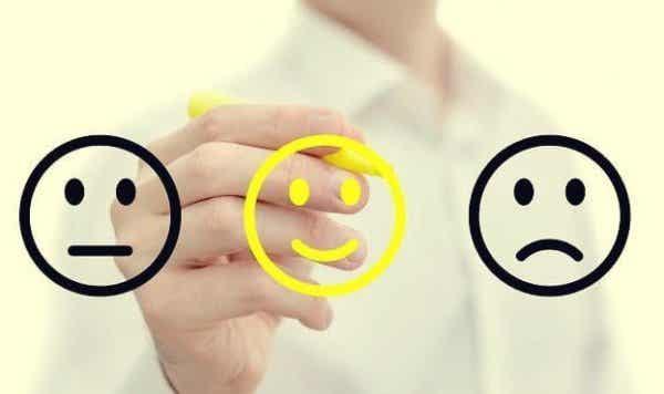 Osoba rysująca szczęśliwe i smutne buźki