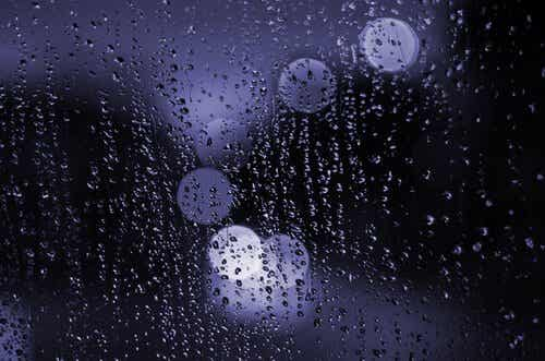 Światło odbijające się w oknie z deszczem