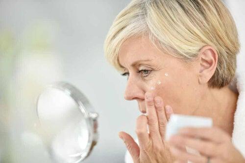Kobieta smarująca twarz kremem