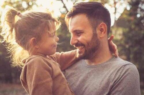 Tata trzymający córkę - jak zbudować relację pełną zaufania z dzieckiem?