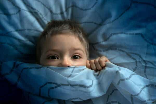 Przestraszony chłopiec pod kołdrą - zespół lęku uogólnionego u dzieci